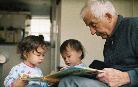 Grandfather Reading to Baby Twins