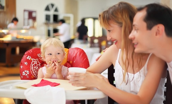 Happy Baby with Parents Dining at Restaurant