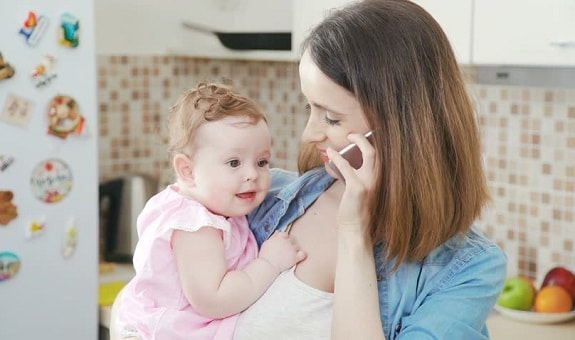 Mother on Phone Holding Baby