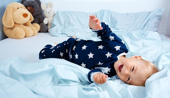 Smiling Toddler Laying in Toddler Bed