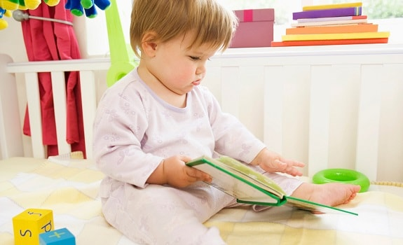 Toddler Playing With Book in Crib