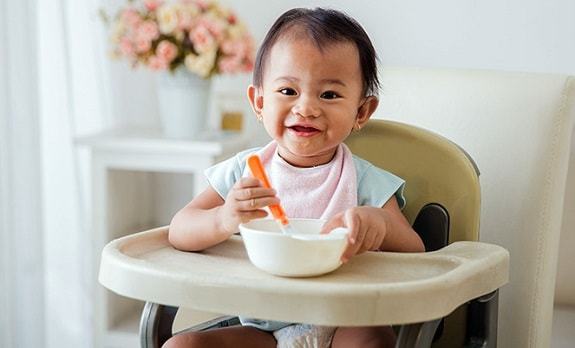 Baby Eating Bowl of Food