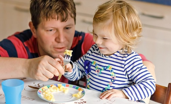 Father Teaching Daughter to Use Fork