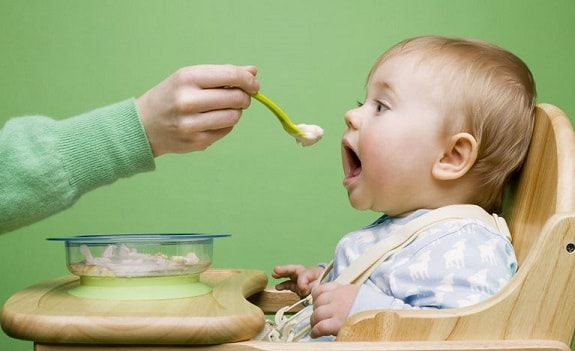 Mother Spoon Feeding Baby Solid Food